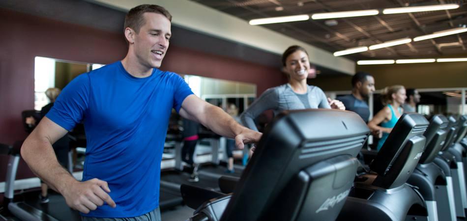 Трениращи във фитнес залата с бягащи пътеки Life Fitness