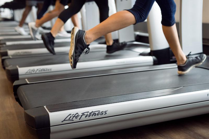 Хора тичащи на бягащи пътеки в зала