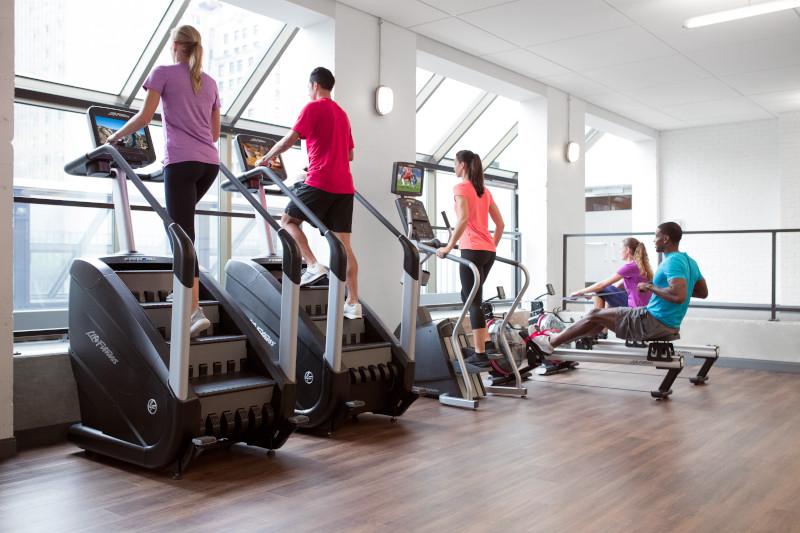 Спортуващи в малка зала с кардио оборудване от Life Fitness