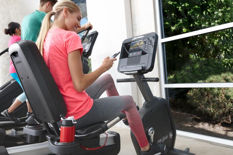 Млада жена проверява телефона си след кардио тренировка на велоергометър Integrity